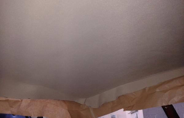 Dann wird erst die vordere, danach dir rückseitige Hälfte des Himmels und des Daches mit dem Kleber eingestrichen oder eingesprüht. Entlang der auch hier gezeichneten Mittellinie wird der Himmelstoff dann vorsichtig (nicht seitlich verziehen, keine Falten schlagen) und zügig angedrückt. Wer sich verklebt, muss großzügig wieder abziehen und neu verkleben, sonst hält das nicht mehr. Tipp: Hierbei weiße Stoffhandschuhe tragen, damit die Werkstattfinger sich nicht auf dem neuen, hellen Material verewigen.