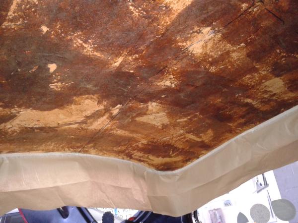 Dies ist die Sich auf das bereits gereinigte Trägermaterial (hier ist es eine Art GFK). Es Dürfen keine Reste mehr vorhanden sein, eventuelle Risse und Brüche sind nun zu beheben. Die Verblendung ringsum ist mit Papier abgeklebt und der Innenraum mit Folie ausgelegt.